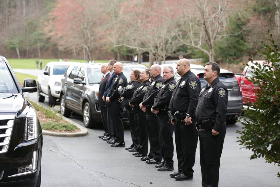Law enforcement officers lined the driveway as the hearse left The Cove.