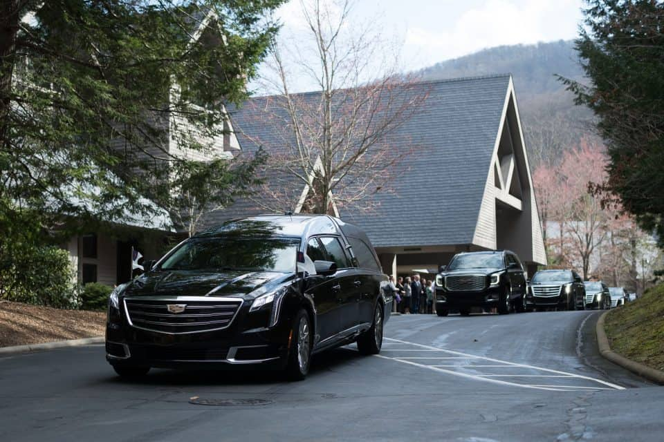 Billy Graham's hearse departed from The Cove around 11:30 a.m. Franklin and Jane Graham drove behind the hearse, followed by Billy Graham's daughters, Anne, Ruth, and Gigi, and their families. Many of Mr. Graham's grandchildren were also part of the procession.