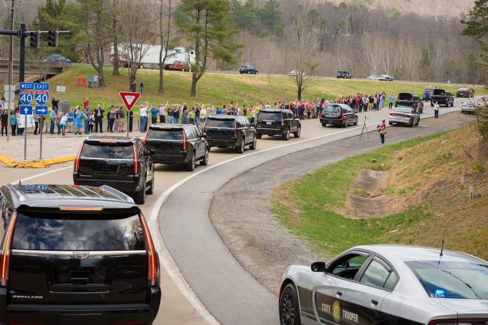 "People parked near the entrance of The Cove and stood by the road to pay their respects as Mr. Graham's hearse passed by on its way to Charlotte, where he was born and raised. ""My father made me promise long ago that we would take him back to Charlotte after he died, and that's what we're in the process of doing right now,"" Franklin Graham said on Saturday."