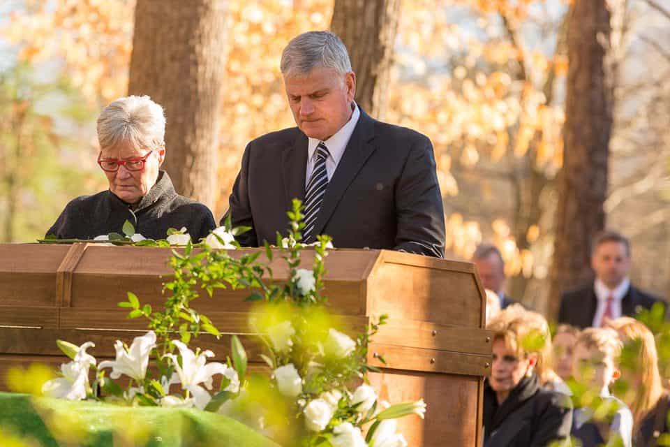 Franklin Graham pauses for a moment of prayer during the interment service.