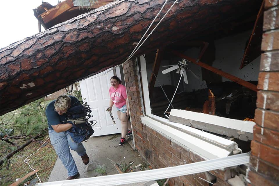 "Residents remove belongings after trees fell on their home in Panama City, Florida. Michael's winds were just shy of a Category 5 hurricane when the storm made landfall. Florida's Gov. Rick Scott called it an ""absolute monster."""