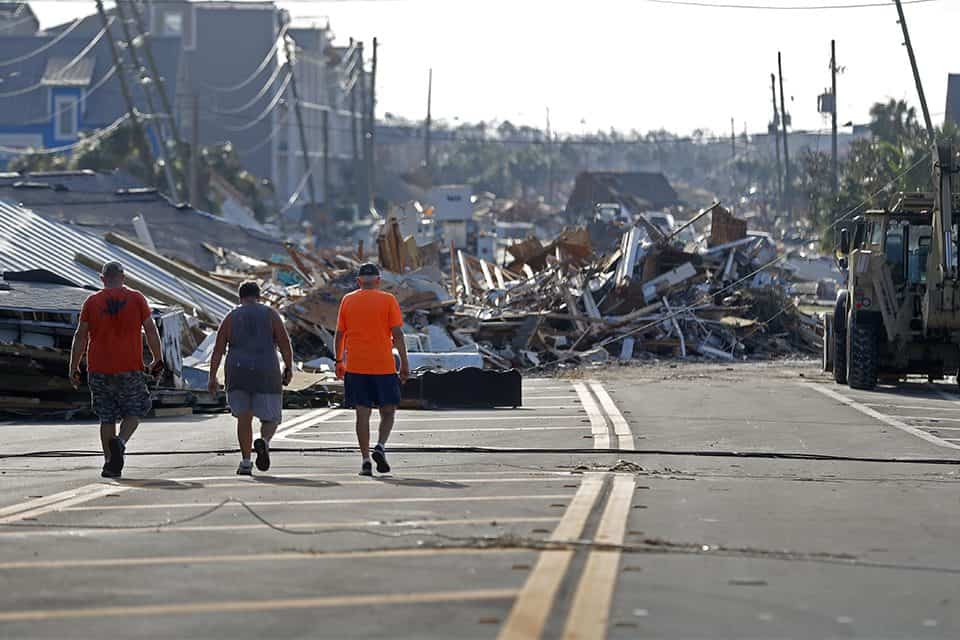People pass by giant piles of destruction on a street framed by downed power lines in Mexico Beach. State agencies and utilities have reported there are more than 1.4 million people left without power from the storm.