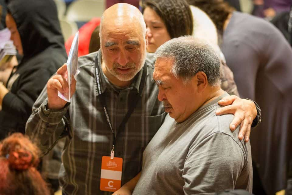A prayer volunteer prays with a man who came forward at Saturday night's invitation to receive Christ as Lord and Savior.