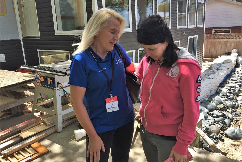 Our Rapid Response Team chaplain prays with an Ottawa flood victim whose home is undergoing sanitization and repairs from water damage.