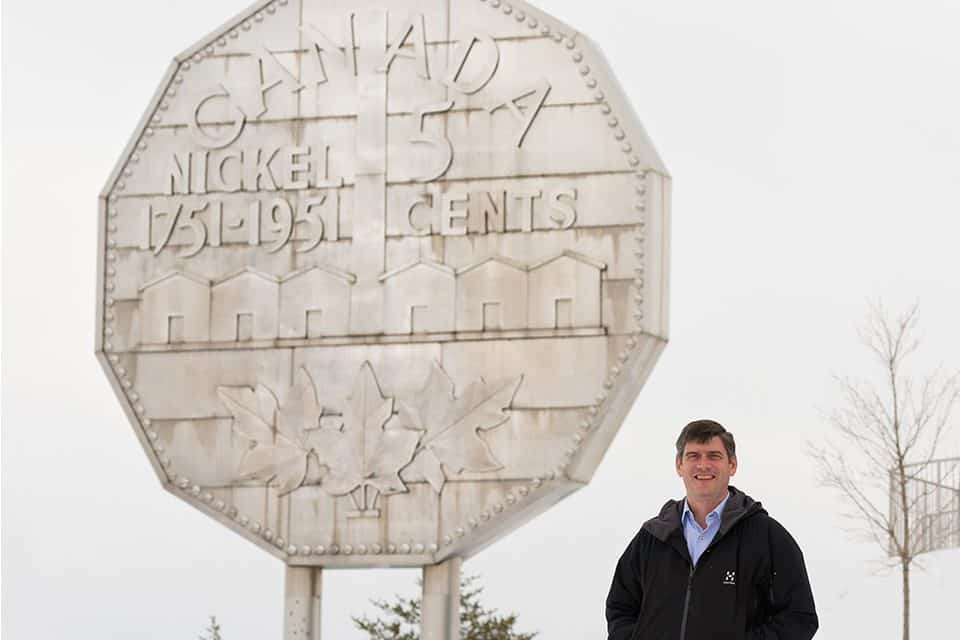 """A lover of the outdoors, Will Graham enjoys visiting Canada, and more importantly, sharing God's love with the nation. Over the past two decades, he's held more than 15 Celebrations there. Here, he poses with the world's largest coin, Canada's """"Big Nickel"""" in Sudbury."""