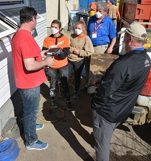 Lauren, a Samaritan's Purse volunteer, presents a Bible to Jonathan, a flood victim, after she and RRT Chaplain Merle Doherty shared the Gospel with him.