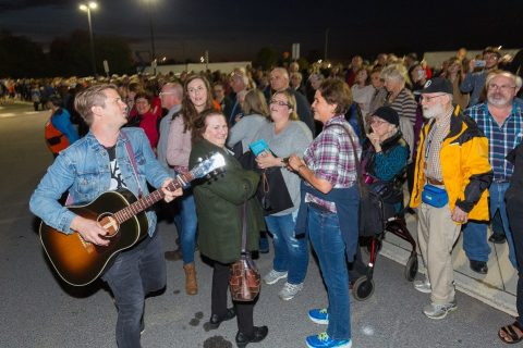 Josh Havens (left), lead singer of The Afters, leading worship in the parking lot during the temporary evacuation of CAA Arena.